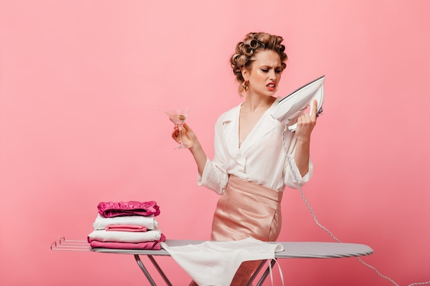 Vrouw in haarkrulspelden kijkt boos naar ijzer en houdt martiniglas
