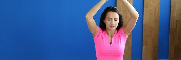 Vrouw in hal zit in lotushouding met haar handen omhoog.