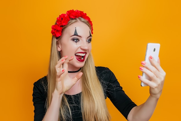 Vrouw in halloween kostuum grimassen en kijkt naar de telefoon