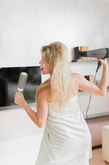 Vrouw in handdoek die haar haarborstel gebruiken als microfoon