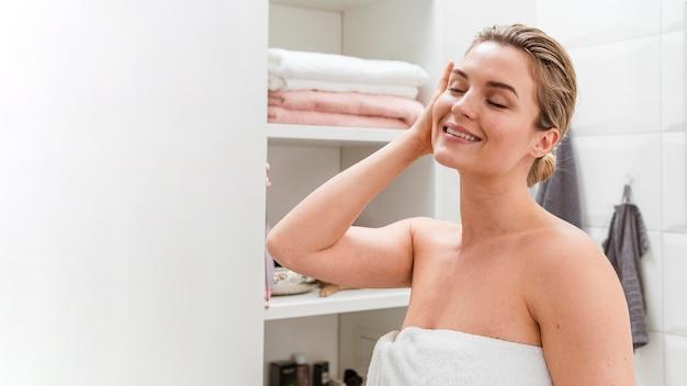 Vrouw in handdoek die in de badkamers is