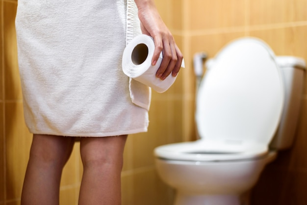 Vrouw in handdoek met toiletpapier rollen in toilet