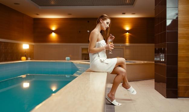 Vrouw in handdoek op het lichaam drinkt thee bij het zwembad