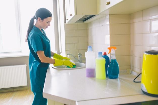 Vrouw in handschoenen die de keuken schoonmaken