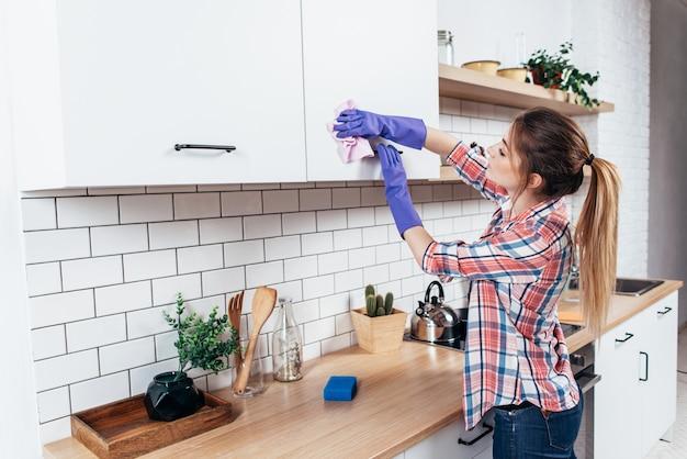 Vrouw in handschoenen die kabinet met lap thuis keuken schoonmaken.