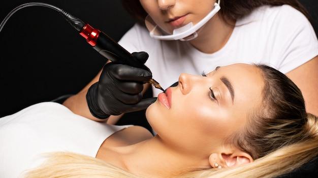Vrouw in handschoenen die permanente lipmake-up maakt aan een mooie blonde vrouw