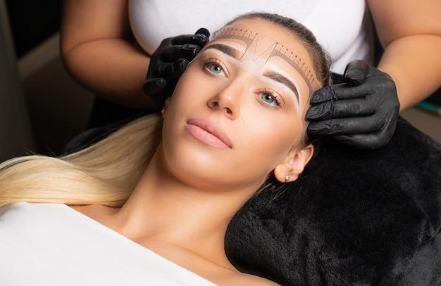 Vrouw in handschoenen die zich voorbereiden op de permanente make-up van het voorhoofd met een liniaal