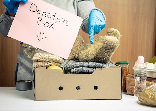 Vrouw in handschoenen houdt een vel papier vast met een donatiebox van letters en een kartonnen doos met eten en dingen om mensen in nood te helpen, vrijwilligershulpconcept