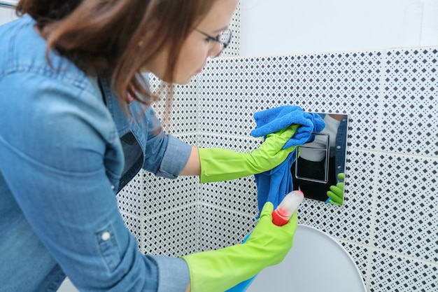 Vrouw in handschoenen met lap die het schoonmaken in badkamers doen, de knoop van het chroomtoilet op betegelde muur oppoetsen