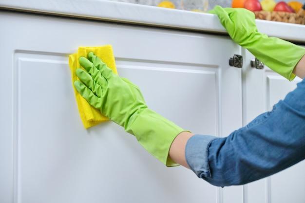 Vrouw in handschoenen met vod die de keuken schoonmaken