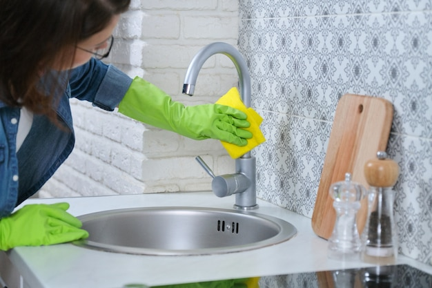 Vrouw in handschoenen met vod die huis in keuken schoonmaken.