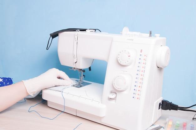 Vrouw in handschoenen naait een beschermend gezichtsmasker op een naaimachine