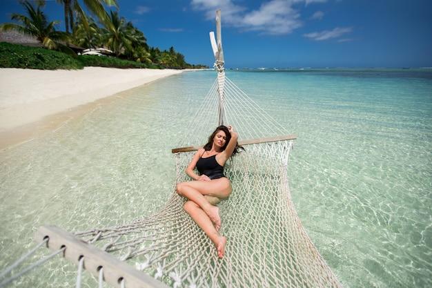 Vrouw in hangmat op tropisch strand op het eiland