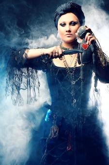 Vrouw in heksen kostuum met voodoo-pop in de hand