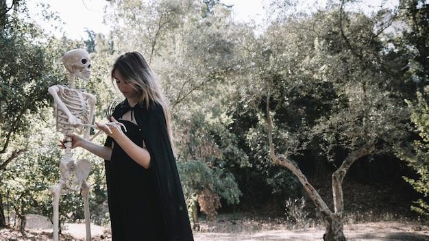 Vrouw in heksenkleren die nauwkeurig skelet houden