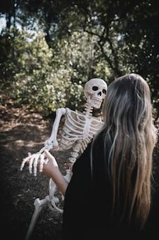 Vrouw in heksenkostuum buigend skelet