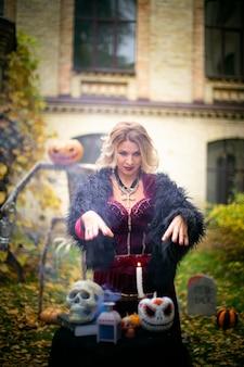 Vrouw in heksenkostuum tovert tafel van een tovenares met schedels en pompoen versierd