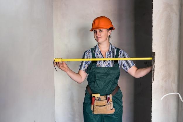Vrouw in helm en beschermend uniform poseren met meter