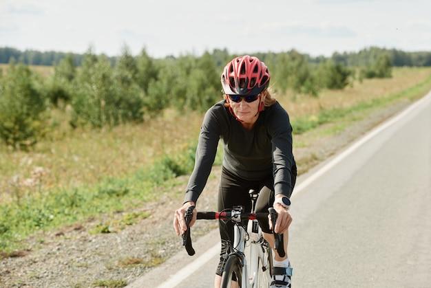 Vrouw in helm en in sportkleding racen op de fiets op een weg buitenshuis