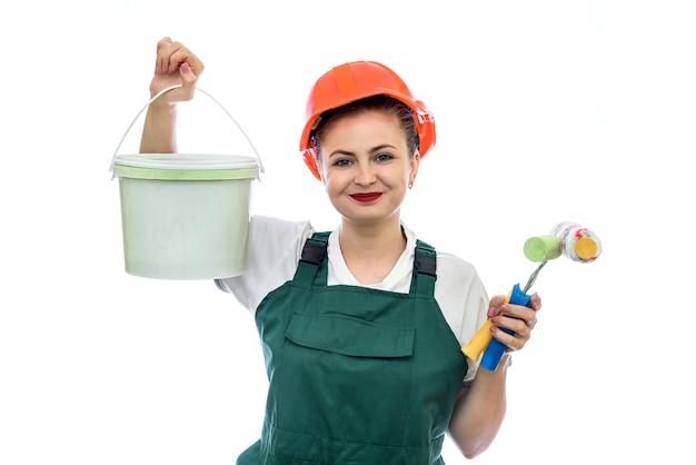 Vrouw in helm met verfemmer die op wit wordt geïsoleerd