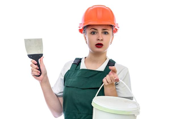 Vrouw in helm met verfemmer die op witte muur wordt geïsoleerd