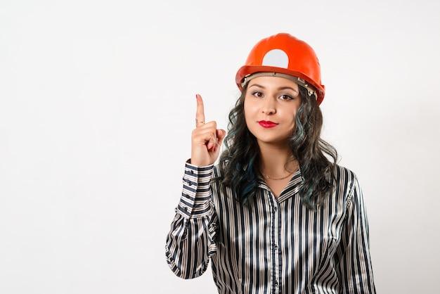 Vrouw in helm wijst vinger naar kopieerruimte op wit