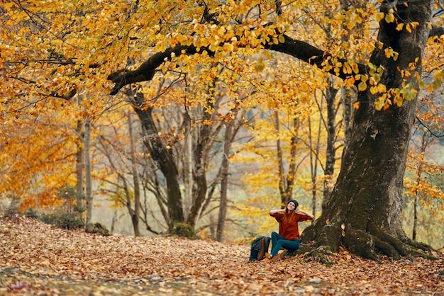 Vrouw in herfst bos zittend onder een boom landschap gele bladeren model