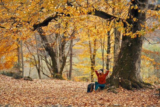 Vrouw in herfst bos zittend onder een boom met gele bladeren