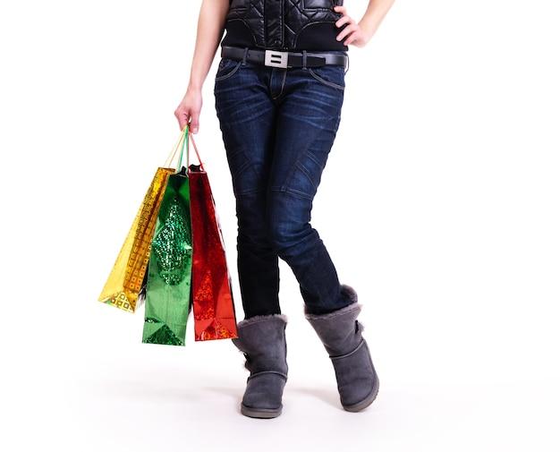 Vrouw in herfst laarzen en blauwe spijkerbroek met boodschappentassen staan - geïsoleerd op wit.