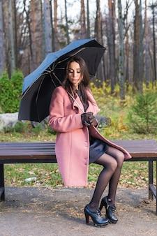 Vrouw in herfst park poseren met paraplu en zittend op de bank.