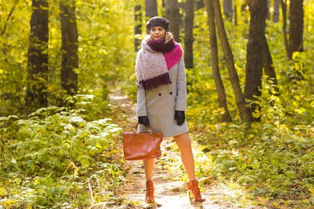 Vrouw in herfst park poseren met tas