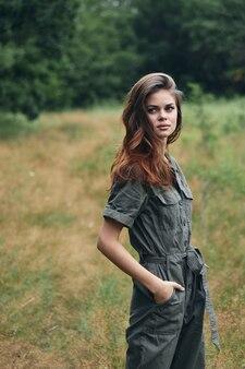 Vrouw in het bos droog gras grijze jumpsuit zijaanzicht