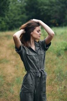 Vrouw in het bos droog gras rood haar groen pak