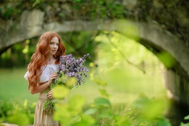 Vrouw in het bos met een boeket bloemen