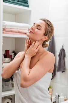 Vrouw in het concept van de handdoek zelfzorg thuis