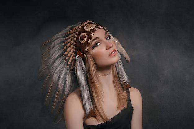 Vrouw in het gewaad van amerikaanse indianen op een grijze achtergrond