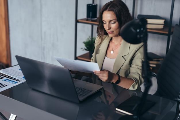 Vrouw in het kantoor achter haar bureau aan het werk, met een vel papier in haar hand.