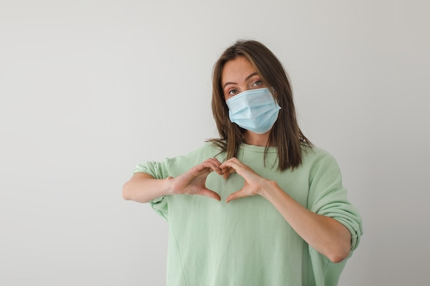 Vrouw in het medische hart van maskerhanden