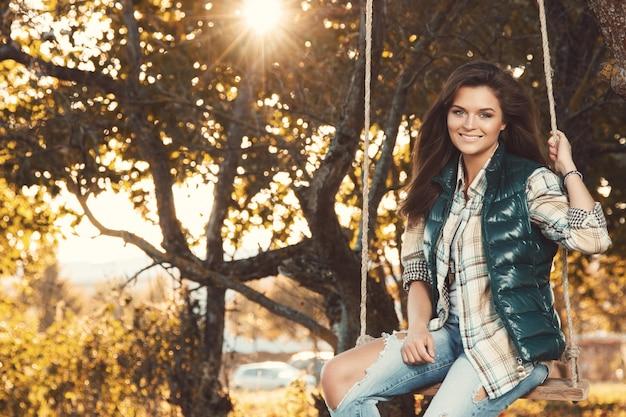 Vrouw in het park bij zonnige de herfstdag