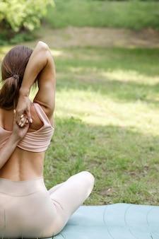Vrouw in het park die yoga van achteren doet