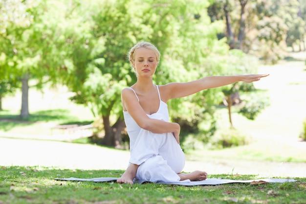 Vrouw in het park die yogaoefeningen doen