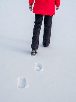 Vrouw in het rode jasje die op sneeuw loopt, voetafdrukken in sneeuw, erachter.