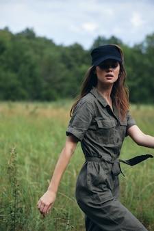 Vrouw in het veld in een groen pak, een zwarte reispet, frisse lucht