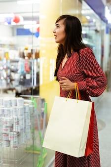 Vrouw in het winkelcentrum met boodschappentassen