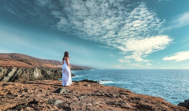 Vrouw in het wit kijkend naar de oceaan op een rotsachtige klif.