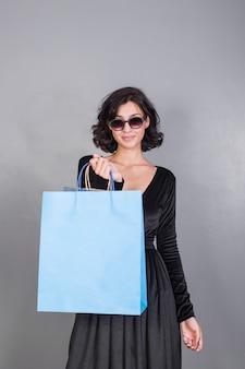 Vrouw in het zwart met blauwe boodschappentas
