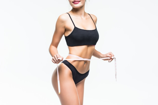 Vrouw in het zwarte ondergoed dat haar taille met metertape meet die op witte muur wordt geïsoleerd