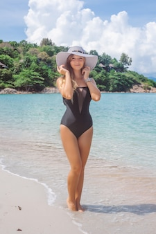 Vrouw in het zwarte zwempak op het strand
