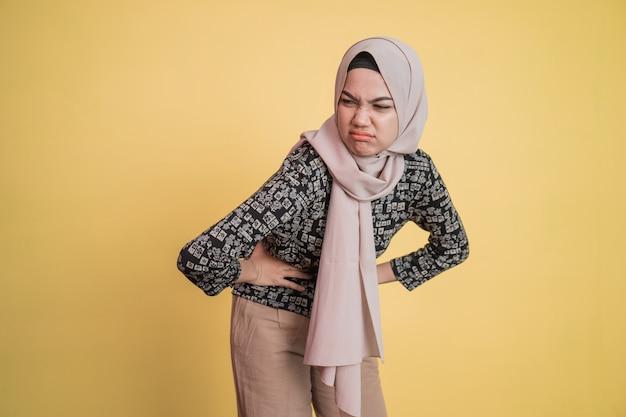 Vrouw in hijab die maag met beide handen vasthoudt met pijnuitdrukking