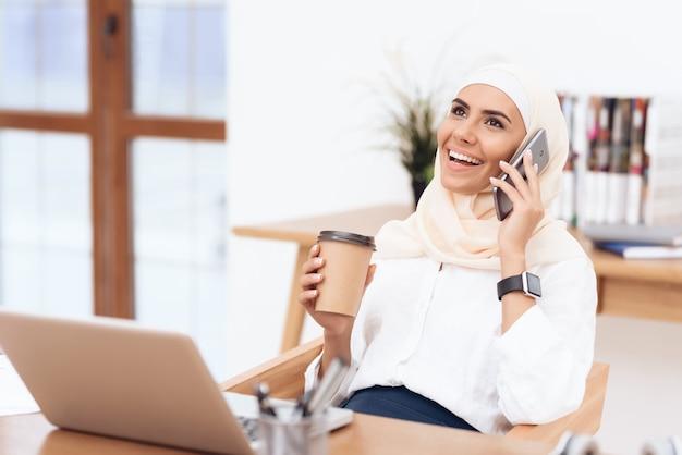 Vrouw in hijab luistert naar muziek op koptelefoon.